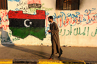 A man walking past a mural showing the map of Libya in the colours of the flag of Free Libya, the symbol of the revolution. The flag was used by the pre Gadaffi monarchy. On 17 February 2011, an uprising against the 41 year rule of Col Muammar Gadaffi started in eastern Libya...