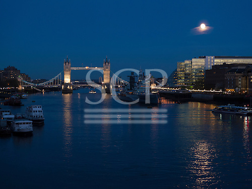London, England. Along the Thames by night, Tower Bridge  and  moon.