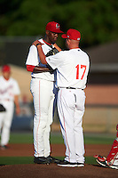 Auburn Doubledays pitching coach Tim Redding (17) talks with starting pitcher McKenzie Mills (14) during a game against the Mahoning Valley Scrappers on July 19, 2016 at Falcon Park in Auburn, New York.  Mahoning Valley defeated Auburn 9-1.  (Mike Janes/Four Seam Images)