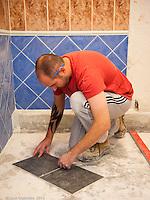 Trainee tiler positioning tiles,  Able Skills training centre, Dartford, Kent.