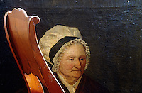 A chair back partially obscures a portrait of an old woman