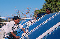 INDIA Rajasthan Mt. Abu , man clean solar collectors on rooftop at Brahma Kumari Ashram building / INDIEN Mann reinigt Solarkollektoren auf dem Dach eines Gebaeude des Brahma Kumari Ashram in Mount Abu