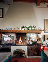 The kitchen range retains its log fire while also having the modern comforts of a gas oven. Behind the appliances are hand painted Neapolitan tiles with functional pot lid holders above.