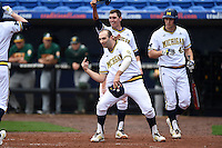 Michigan Wolverines Jackson Glines (27), Eric Jacobson (12) and Carmen Benedetti (43) wait for Travis Maezes (left) after hitting a home run during the first game of a doubleheader against the Siena Saints on February 27, 2015 at Tradition Field in St. Lucie, Florida.  Michigan defeated Siena 6-2.  (Mike Janes/Four Seam Images)