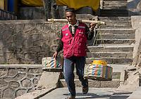 Nepal, Kathmandu, Swayambhunath.  Man Using a Shoulder Pole to Carry a Load.