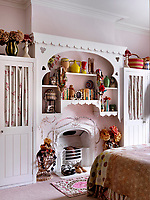 In the master bedroom an ornate custom shelving has been created above an original Victorian fireplace