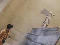museo del Louvre. turista con mascgerina osserva la Nike