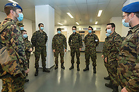 """Switzerland. Canton Ticino. Locarno. Ospedale Regionale di Locarno La Carità. Due to the spread of the coronavirus (also called Covid-19), the Federal Council has categorised the situation in the country as """"extraordinary"""". The army was called upon to provide its troops in terms of medical assistance. The militia soldiers from medical troops were called by the Swiss army for the first time since World War II. Under the country's militia system, professional soldiers constitute a small part of the military and the rest are conscripts or volunteers aged 19 to 34 (in some cases up to 50).  All men and a woman, dressed with camouflage uniforms, stand inside the main entrance to the hospital.They all were a mask to protect themselves from the coronavirus ( also called Covid-19).  20.11.2020 © 2020 Didier Ruef"""