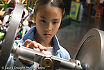 8 year old girl adjusting weight on exhibit device at Exploratorium The Museum of Science,Art, and Human Perception in San Francisco CA USA horizontal
