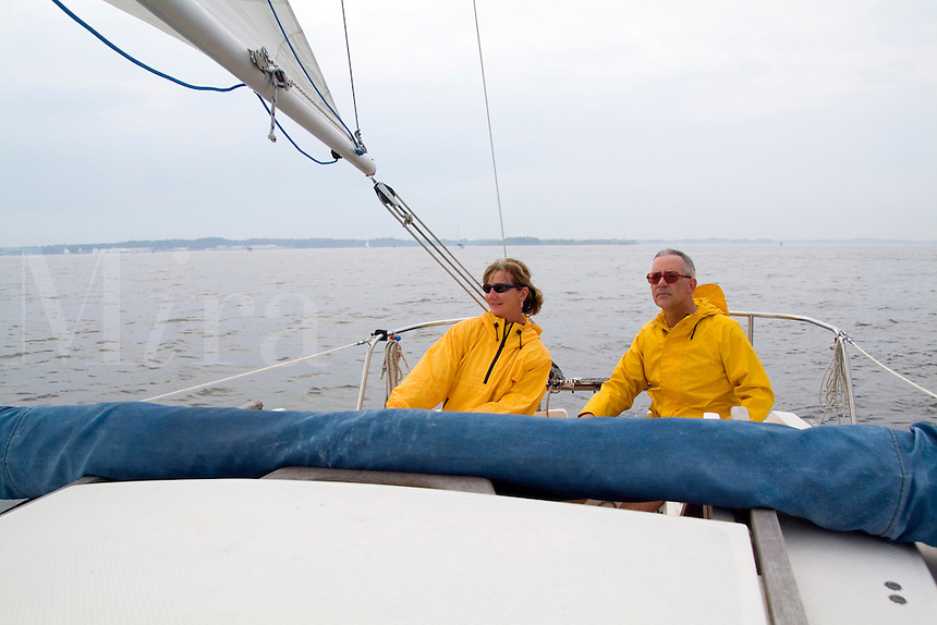 Couple in yellow slickers sailing small sailboat for fun on Chesapeake in Maryland USA