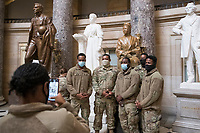 Members of the National Guard take photos next to the statue of Rosa Parks in Statuary Hall of the U.S. Capitol, as the House of Representatives vote on H. Res. 24, Impeaching Donald John Trump, President of the United States, for high crimes and misdemeanors, at the U.S. Capitol in Washington, DC, Wednesday, January 13, 2021. Credit: Rod Lamkey / CNP /MediaPunch