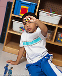Education preschool 4 year olds boy playing by himself with human figure talking and moving it in the air