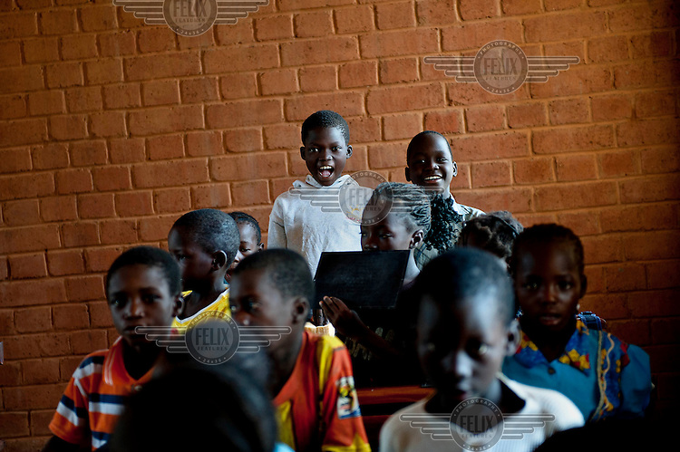 """Children sing during a lesson at the newly opened school in the Opera Village. The """"Opera Village"""" is the brainchild of the late German theatre and film director Christoph Schlingensief who died of cancer in 2010. He wanted to create an African site similar to Bayreuth in Germany which has become the world centre for Wagner music. ."""