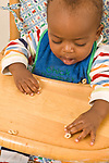 9 month old baby boy sitting in high chair reaching and grasping Os cereal with pincer grasp