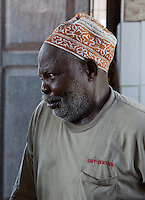 Zanzibar, Tanzania.  Darajani Fish Market, Stone Town.  Man Watching an Auction, wearing a traditional Zanzibari hat, a kofia.