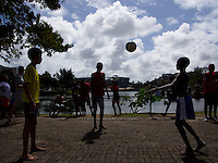 Kids playing football in front of the Arena Fonte Nova in Salvador