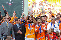 Houston Dynamo midfielder (14) Dwayne De Rosario hoists the MVP trophy. The Houston Dynamo defeated the New England Revolution 2-1 in the finals of the MLS Cup at RFK Memorial Stadium in Washington, D. C., on November 18, 2007.