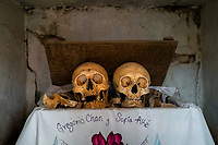 """Dried-up sculls and bones are seen wrapped in a cloth and placed in a wooden crate inside a niche at the cemetery in Pomuch, Mexico, 26 October 2019. Every year on the Day of the Dead, people of Pomuch, a small Mayan community in the south of Mexico, visit the cemetery to take part in a pre-Hispanic tradition of cleaning of bones of their departed relatives (""""Limpia de huesos""""). People who die in Pomuch are firstly buried for three years in an above-ground tomb then the dried-up bodies are taken out, bones are separated, wrapped in a decorated cloth, put into a wooden crate, and placed on display among flowers for veneration."""