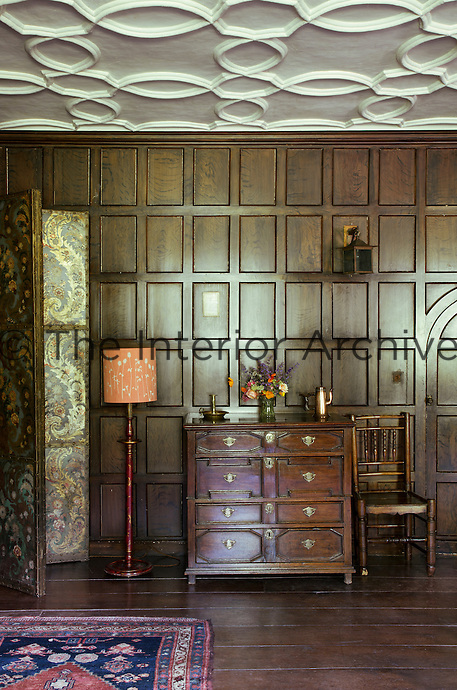 Detail of a the chest of drawers and other antique furniture in a panelled bedroom