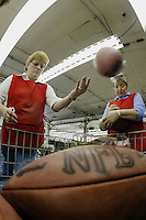 20 January 2005: Rose Sanders, left, and Pam Clark inspect footballs at the Wilson football factory where Super Bowl footballs are made Thursday January 20, 2005 in Ada, Ohio.<br />