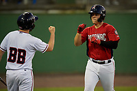 Potomac Nationals KJ Harrison (12) fist bumps the bat boy after hitting a home run during a Carolina League game against the Myrtle Beach Pelicans on August 14, 2019 at Northwest Federal Field at Pfitzner Stadium in Woodbridge, Virginia.  Potomac defeated Myrtle Beach 7-0.  (Mike Janes/Four Seam Images)