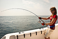 This woman in her late 30s is fighting a Giant Trevally, a tropical gamefish with rod and reel