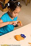 Preschool ages 3-5 art activity play dough girl using scissors on play dough vertical