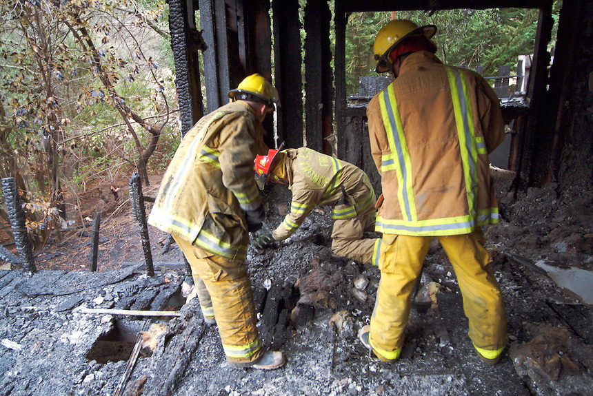 Fire fighters from several agencies investigate the cause of a structure fire on Dupont Road in Occidental, California, USA.