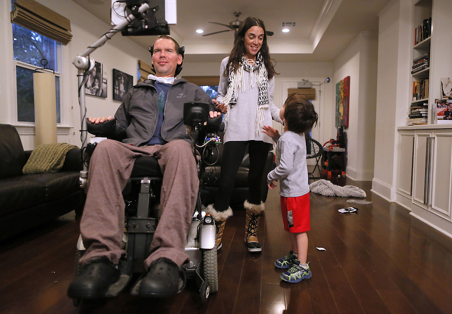 """In this Monday, Jan. 18, 2016 photo, former New Orleans Saints NFL football player Steve Gleason and his wife, Michel, pause to talk to their 4-year-old son, Rivers, during an interview in New Orleans. """"GLEASON,"""" a feature-length documentary that gives an unfiltered look at his life with ALS premieres at the Sundance Film Festival on Saturday. (AP Photo/Jonathan Bachman)"""