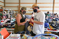 """Maris Moon (from left) and Kyle Cook of Bentonville shop, Thursday, October 7, 2021 during a rummage sale at the Central United Methodist Church in Rogers. The annual event returns with a larger selection for shoppers following a break due to the covid-19 pandemic. """"We're inundated this year,"""" said Carol Hartman, president of the  Central United Methodist Women. """"[donors] stayed home and cleaned out their houses, and so they had lots to donate this year."""" Items included houseware and clothing as well as unique items like an armoire of clothing from the 1880's and a Gucci watch. All funds from the sale will go to support projects for women and children in the community and world wide. Check out nwaonline.com/211008Daily/ for today's photo gallery. <br /> (NWA Democrat-Gazette/Charlie Kaijo)"""