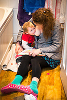A woman breastfeeds her 20 month old toddler while reading a book her.  The little girl is sitting on her potty.<br /> <br /> 07/02/2013<br /> Hampshire, England, UK