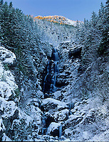 Waterfalls in winter below a ridge with larch trees still in fall colors, North Cascades Mountain Range, Washington State.