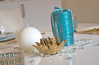 Table Accessories, white ball candle, cylindrical metallic turquoise candle with a ribbon, and a shiny golden artificial blossoming flower, on a white dining table.