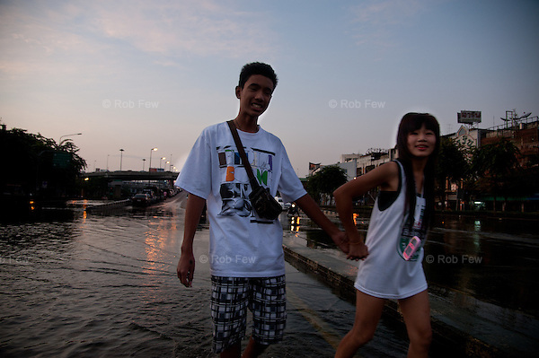 A young couple walk through flood water in western Bangkok.<br /> <br /> Thailand's worst floods for 50 years finally reached the suburbs of Bangkok in October 2011. While the government dithered and argued with itself, more than 200 people died.