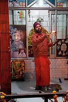 India, Rishikesh.  Hindu Priest Saying Early Morning Prayers at a Shrine.