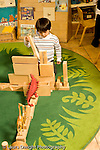 Education Preschool 3-5 year olds boy working on long block construction plastic toy animals giraffes and dinosaurs set up on blocks vertical