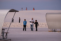 People walk among the curved picnic shelters in a parking area during sun set at White Sands National Monument near Alamogordo, New Mexico, USA, on Sat., Dec. 30, 2017.