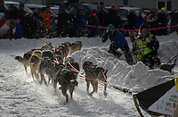 Peter Kaiser's team rounds the corner at Cordova street during the 2016 Iditarod Ceremonial Start in downtown Anchorage. Photo by James R. Evans