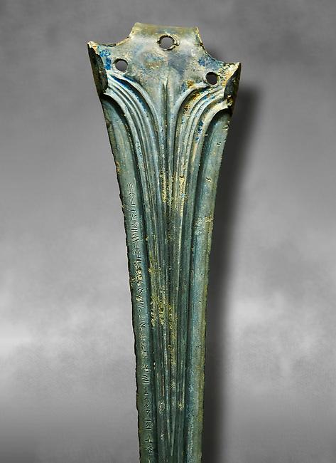 Hittite bronze decorated sword blade close up with writing. Hittite Period 1650 - 1450 BC.  Hattusa Boğazkale. Çorum Archaeological Museum, Corum, Turkey. Against a grey bacground.