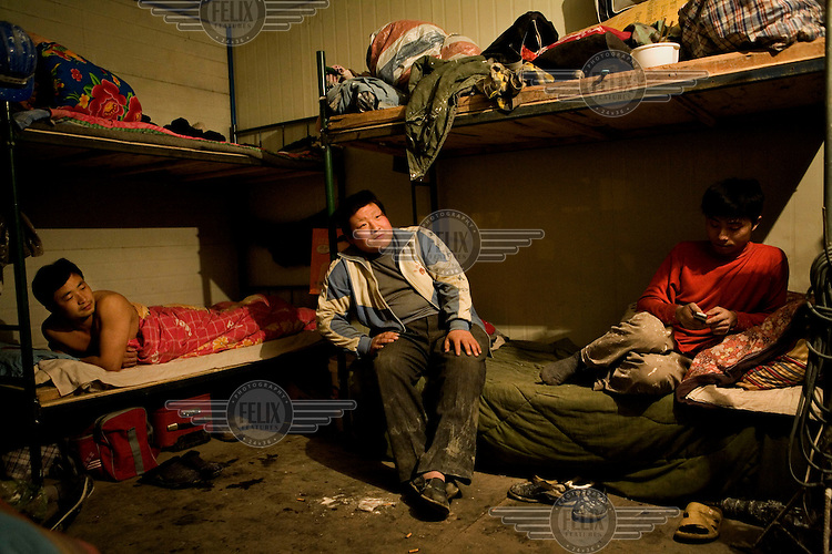 Migrant workers in their dormitory accomodation. Chen, who sits in the middle, is only 17 years old whilst the others are in their mid twenties.