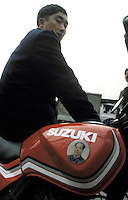 A man rides on a motorbike with Mao's sticker.