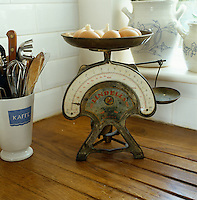 An antique weighing scales is used to store eggs and garlic