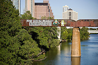 """The most famous street art in Austin is on a bridge over Lady Bird Lake, the """"Let's Pretend We Are Robots"""" graffiti mural painting on the Austin Railroad Bridge over Lady Bird Lake."""