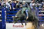 Professional Bull Riders in action during the Frontier Communications Iron Cowboy bull riding event, at the AT & T stadium in Arlington, Texas.