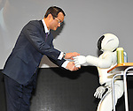 November 30, 2011, Tokyo, Japan - Takanobu Ito, president of Honda, is waited on with a cup of tea by Ashimo, human-shaped robot developed by the automaker, during a press preview of the Tokyo Motor Show on Wednesday, November 30, 2011...The Tokyo Motor Show opened to the press Wednesday as Japanese automakers unveiled a bevy of electric cars and other green vehicles at a much smaller venue in central Tokyo, to which the show moved from the nations largest exhibition hall in neighboring Chiba prefecture after 24 years. A total of 176 brands from 13 countries and regions participated in the show. The number of foreign automakers has increased to 24 from previous nine. Out of 398 models, 52 will be shown for the very first time. An estimated 800,000 visitors are expected to attend the week-long exhibition, compared with 1.5 million in 2005, according to the organizers.(Photo by Natsuki Sakai/AFLO) [3615] -mis-.