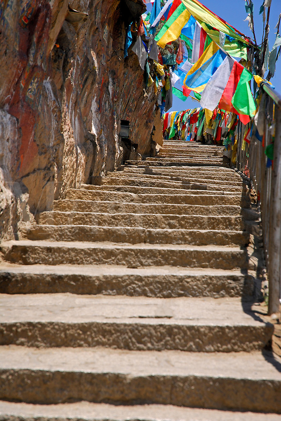Path lined with prayer-flags and painted rock carvings is part of the sacred Lingkhor pilgrim circuit, encircling the old city, as it ascends Chagpo Ri mountain, Lhasa, Tibet, China.