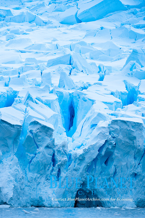 A glacier fractures and cracks, as the leading of a glacier fractures and cracks as it reaches the Ocean  The pieces will float away to become icebergs.