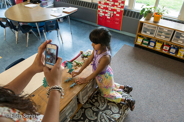 MR / Schenectady, NY. Zoller Elementary School (urban public school). Kindergarten classroom. Teacher uses smartphone camera to photograph student (girl, 5, biracial) at play. Photographs in this classroom are used as an assessment tool for student's cognitive, emotional, and social growth throughout the schoolyear. MR: Myk1. ID: AM-gKw. © Ellen B. Senisi.