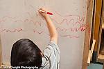 "Preschool 2-3 year olds boy ""writing"" with dry erase marker on board horizontal"