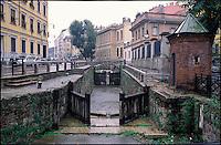 """Milano, la Conca dell'Incoronata (o delle Gabelle) sotto la pioggia. La chiusa è l'unico resto del Naviglio Martesana all'interno del centro storico milanese. Nella foto: le porte vinciane, la garitta in mattoni e l'ultimo ponte antico --- Milan, the """"Conca dell'Incoronata"""" under rain. The canal pound is the only remain of the Naviglio Martesana in downtown. In the picture: the Da Vinci's locks, the sentry box and the last existing ancient bridge"""